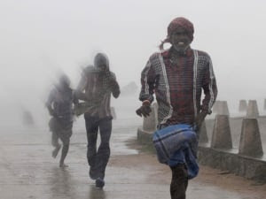 People run for shelter as heavy rain and wind gusts rip through the Bay of Bengal coast at Gopalpur, Orissa on Sunday, Oct. 12, 2014.