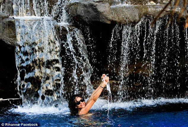 Topless: The singer goes topless in a pool beneath a water fall as she strikes a series of poses for the camera