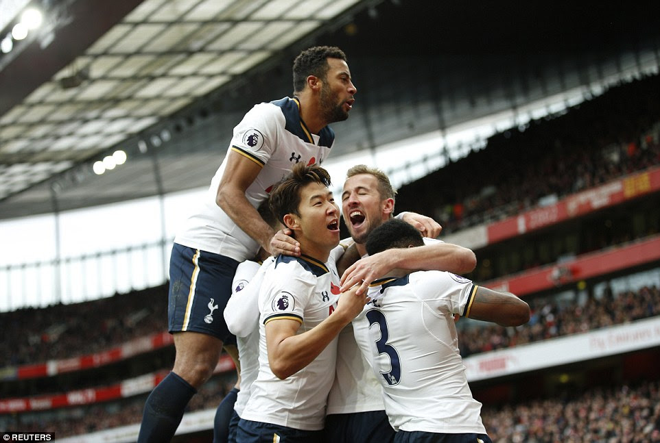 Kane is surrounded by his team-mates after he levelled the scoreline following a foul by Koscielny on Dembele