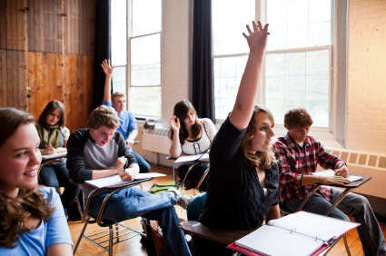 High School students in a classroom raising their hands.