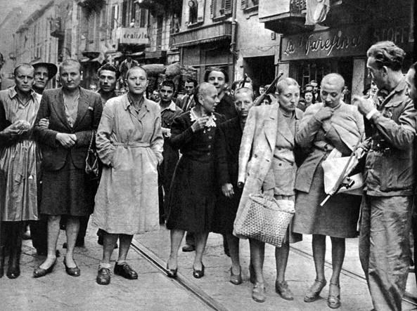 Un gruppo di ausiliarie fasciste aderenti alla Repubblica sociale italiana rasate a zero subito dopo la Liberazione e portate in giro dai partigiani vittoriosi per le strade di Milano (Foto Lapresse)
