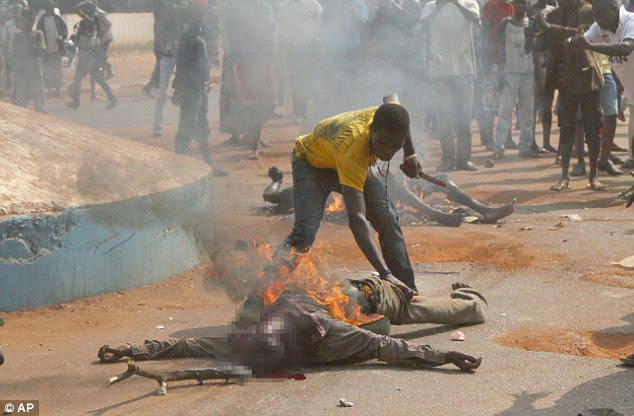 A man who goes by the name of Mad Dog cuts off a portion of a burning body to eat, as the bodies of two lynched Muslim men are burned in a street in Bangui, Central African Republic