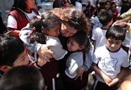A woman comforts her children outside a school at the Roma neighborhood after a earthquake felt in Mexico City Tuesday March 20, 2012. A strong, long earthquake with epicenter in Guerrero state shook central southern Mexico on Tuesday, swaying buildings in Mexico City and sending frightened workers and residents into the streets..(AP Photo/Alexandre Meneghini)