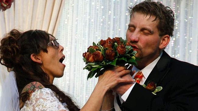 Craig Rouch takes a bite out of his bride April's bacon bouquet before their wedding during the Blue Ribbon Bacon Festival. P...