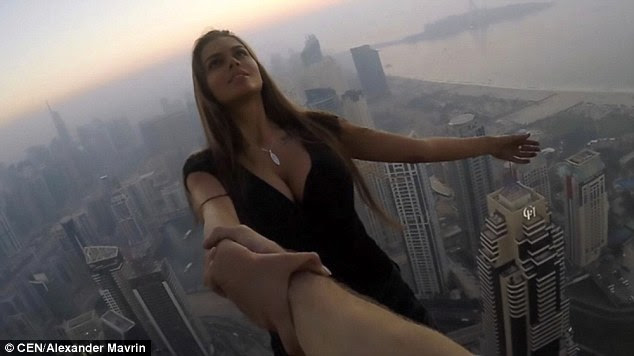 Ms Odintsova, 23, was only held up by the hand of a male assistant as she leaned out into thin air from the 1,004-foot tall Cayan Tower in Dubai