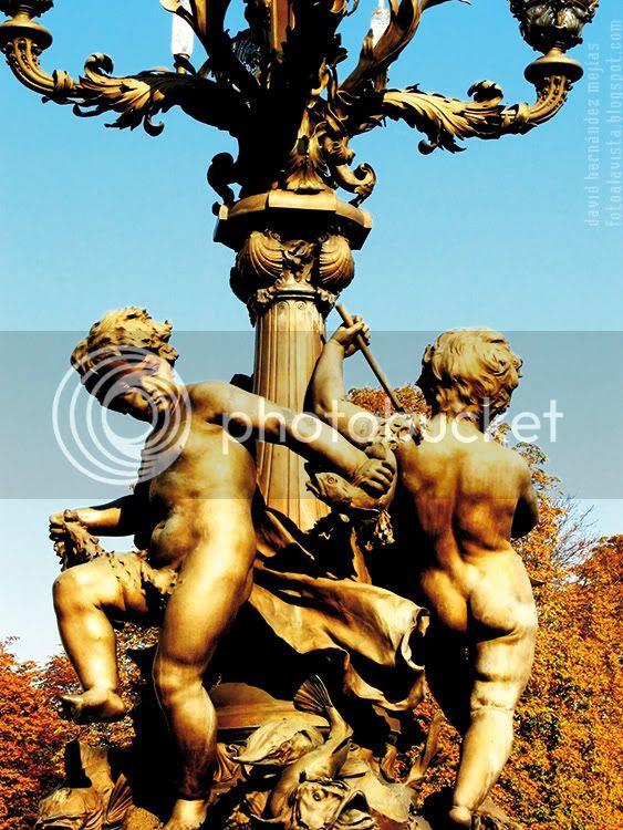 Fotografía de conjunto escultórico de dos niños, que parecen amorcillos, con peces alrededor de una farola sobre el puente de Alejandro III, de París (Francia)