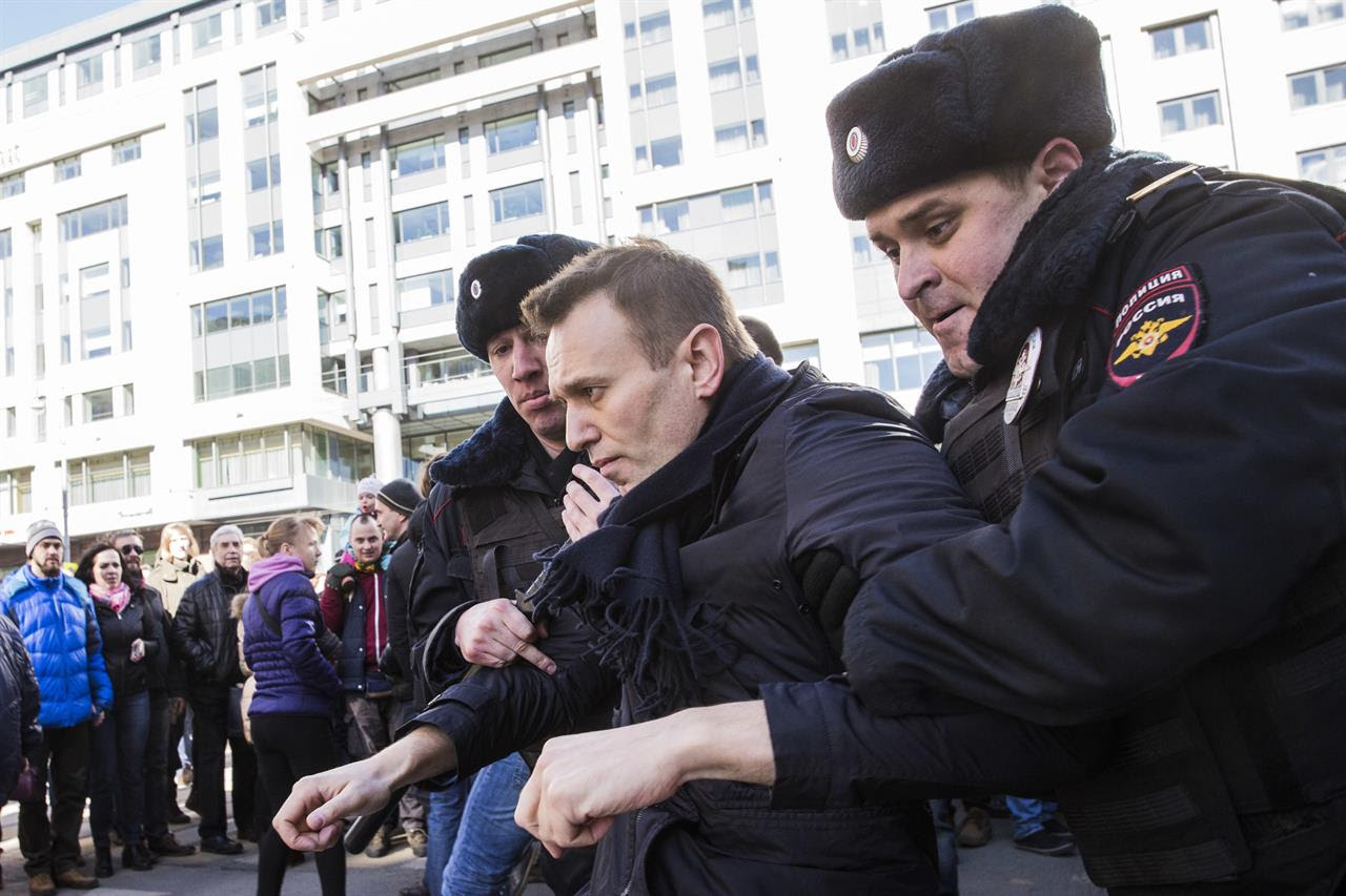 "In this photo provided by Evgeny Feldman, Alexei Navalny is detained by police in downtown Moscow, Russia, Sunday, March 26, 2017. Russia's leading opposition figure Alexei Navalny and his supporters aim to hold anti-corruption demonstrations throughout Russia. But authorities are denying permission and police have warned they won't be responsible for ""negative consequences"" or unsanctioned gatherings."