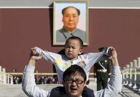 Devant le portrait de Mao Zedong, sur la place Tiananmen, à Pékin.