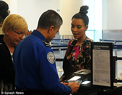 Tickets please: Airport staff check Kim's ticket before she boards her flight