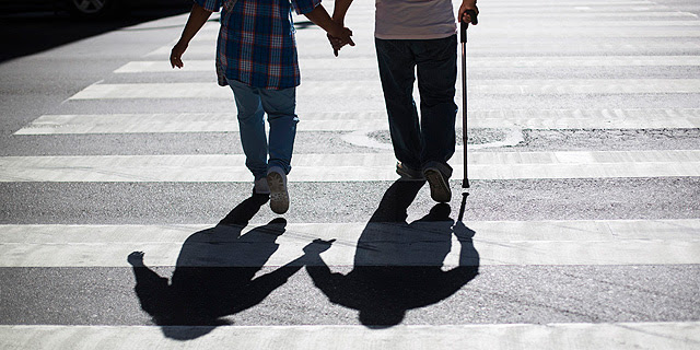 Una pareja cruza la calle con la ayuda de una muleta.| Lucas Jackson
