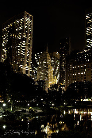 Skyline Reflection of Central Park NYC  by the Plaza and the well known NYC Apple Store. Photo taken from the Gapstow Bridge at the southernmost corner of Central Park near Wollman Ice Skating Rink, yes, the skating rink in almost every movie made in Central Park including Serendipity, Limitless, and Love Story to name a few :)   -   JohnBrody.com / JohnBrody.com Photography