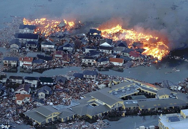 Utter devastation: Flames engulf houses in Sendai, Miyagi, after they were swallowed up by enormous waves that swept through Japan after a massive earthquake this morning