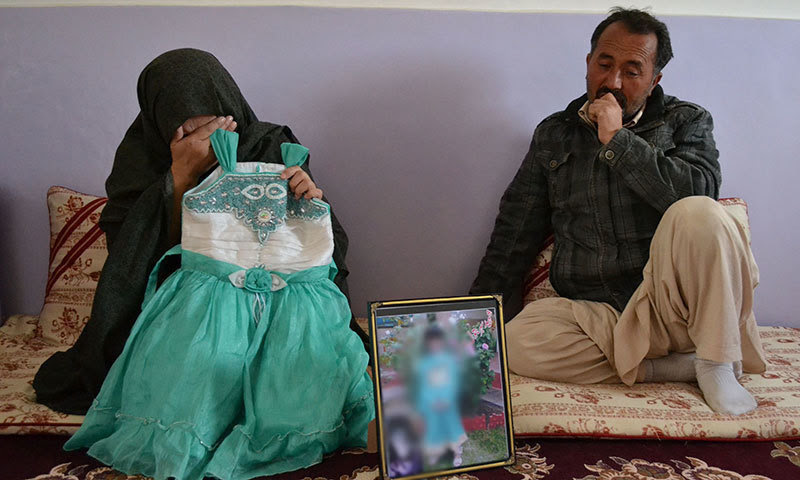 Photo from Nov 7, 2014 shows the parents of Saher Batool mourning while holding their late daughter's dress in Quetta.—AFP
