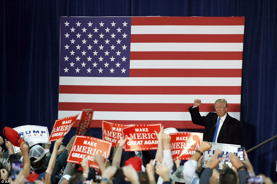 In Vancouver yesterday, Trump pumps his fist at a rally as hundreds of supporters wave signs in the air carrying his famous slogan throughout the campaign: 'Make America great again'