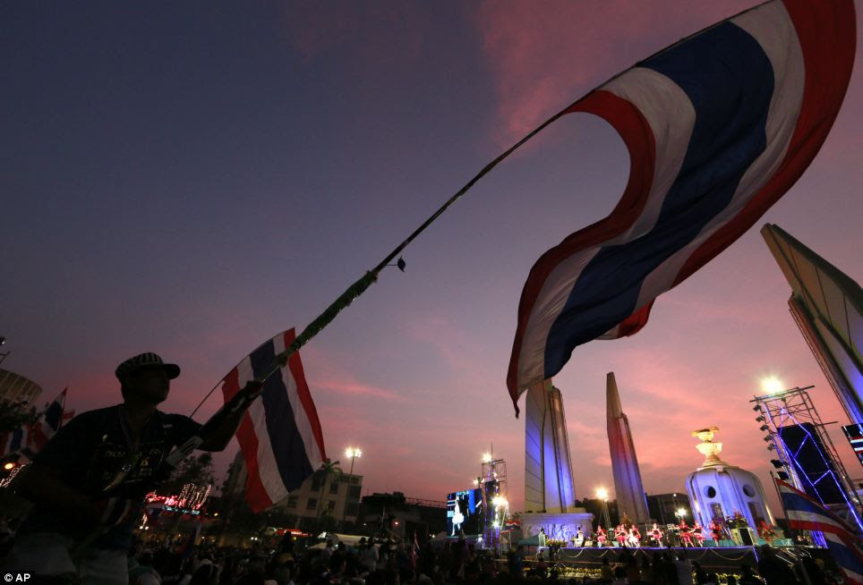 An anti-Thai government protester waves national flag as dancers perform on stage during a New Year's Eve rally at the Democracy Monument in Bangkok, Thailand