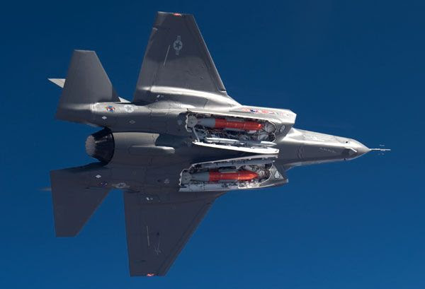 An F-35A Lightning II conducts a flight test with bombs and missiles aboard.