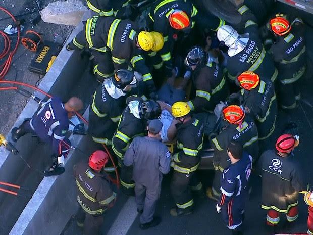 Ferido é retirado por bombeiros de veículo atingido por carreta na Dutra em Guarulhos (Foto: Reprodução/TV Globo)