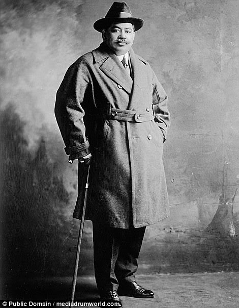 Sporting a moustache, polished shoes, a thick coat over a suit and a cane,Prince J Kalanianole of Hawaii poses for a picture in 1920