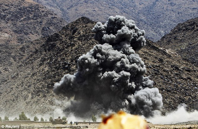 Attacks: An explosion after an airstrike in Nanagarhar, Afghanistan. The report, based on interrogation of insurgents, claims Taliban fighters are being given weapons and training by Pakistan-backed militants