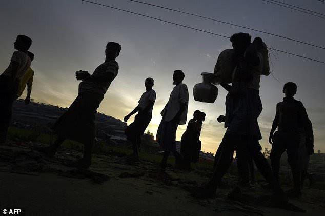 Rohingya rehugees walk along a road on the proximity of the refugee camp of Thwangkhaneari near the Bangladeshi locality of Ukhia