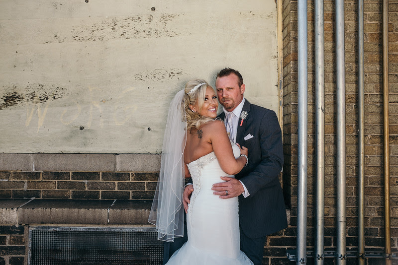 Bride and groom photos in an urban rustic setting and alley after an indoor wedding ceremony at the Armory in Janesville WI on a beautiful late spring day.