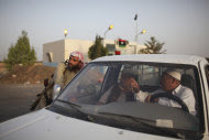 A rebel fighter, left, checks a car at a checkpoint between Tarhouna and Bani Walid, Libya, Monday, Sept. 5, 2011. Negotiations over the surrender of one of Moammar Gadhafi's remaining strongholds have collapsed, and Libyan rebels were waiting for orders to launch their final attack on the besieged town of Bani Walid, a spokesman said. (AP Photo/Alexandre Meneghini)
