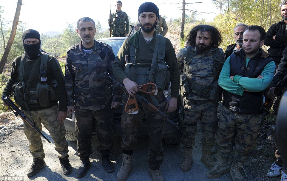 A picture has emerged of Alpaslan Celik (centre), a deputy commander in a Syrian Turkmen brigade, holding handles believed to be parts of a parachute belonging to a pilot of the downed Russian warplane