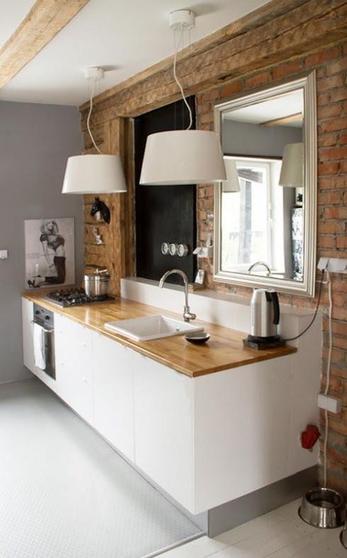 biała kuchnia ze ścianą z czerwonej cegły