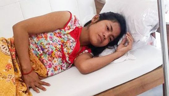 A woman rests on a bed at a Phnom Penh medical clinic after she was injured during a robbery in Russey Keo district early yesterday morning. Photo supplied