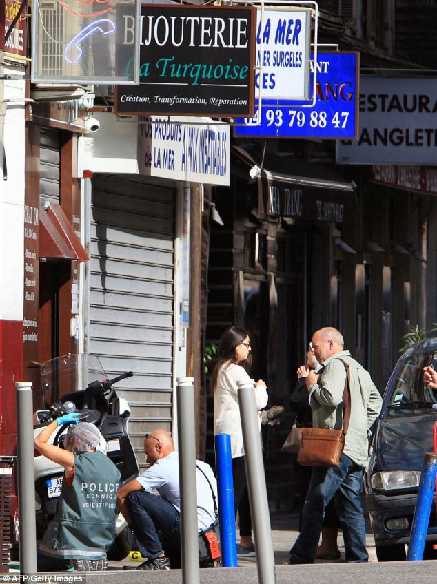 Officers work outside the jewellers La Turquoise which was reportedly robbed shortly before the shooting
