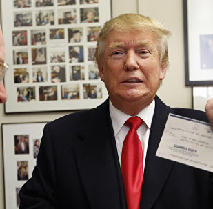 Secretary of State Bill Gardner watches at left as Republican presidential candidate Donald Trump shows off his filling fee check after filing papers to be on the nation's earliest presidential primary ballot.