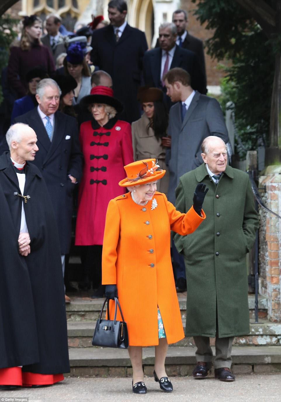 The Queen stood out in the crowd in her bright orange coat as she waved to well-wishers while leaving the church