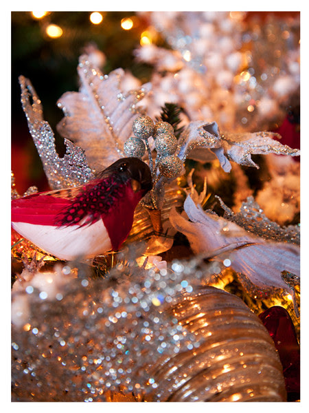 Feathered robin amidst glass ornaments and glitter edged greenery.