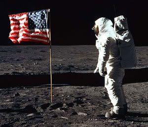 Apollo 11 astronaut Buzz Aldrin stands before an American Flag erected on the lunar surface
