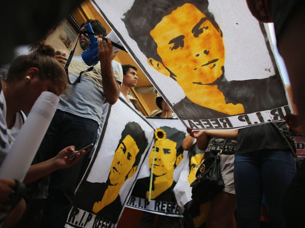 Cartazes mostram o rosto do grafiteiro Israel Hernández, morto pela polícia de Miami após ser atingido por arma de choque; protesto pediu apuração do incidente (Foto: Joe Readle/Getty ImagesAFP)