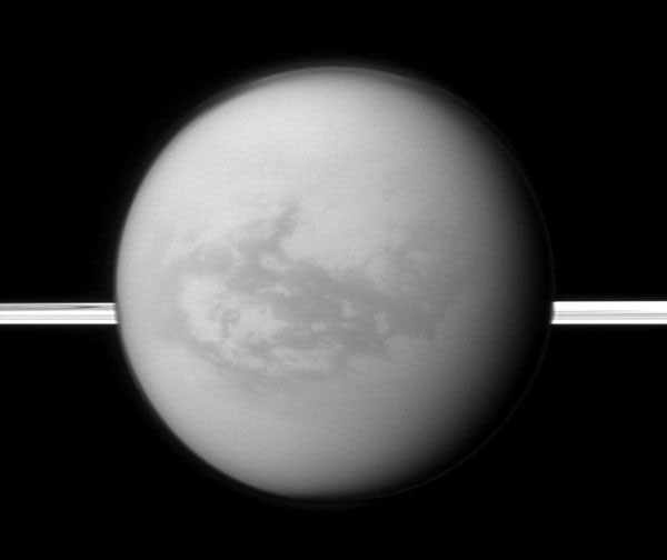 Saturn's rings lie in the distance as the Cassini spacecraft looks toward Titan and its dark region dubbed Shangri-La, on August 9, 2011.