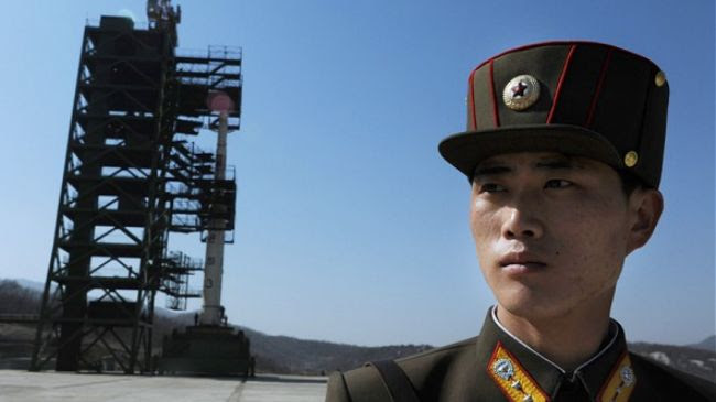 A soldier stands guard in front of the Unha-3 (Milky Way 3) rocket in North Korea.