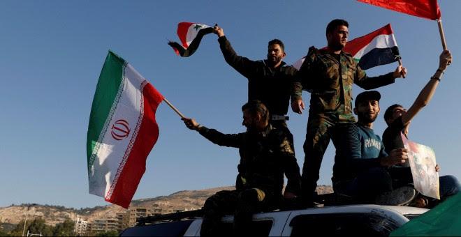 Sirios ondean las banderas de Irán, Rusia y Siria en protesta por los ataques en Damasco. /REUTERS