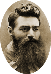 Head of a young man with a long, untrimmed beard, and with hair cropped above the ears, but longer and slicked strikingly up and back on the top. His moustache and beard are so long that his mouth and shirt front can barely be seen. His eyes look over the viewer's right shoulder .
