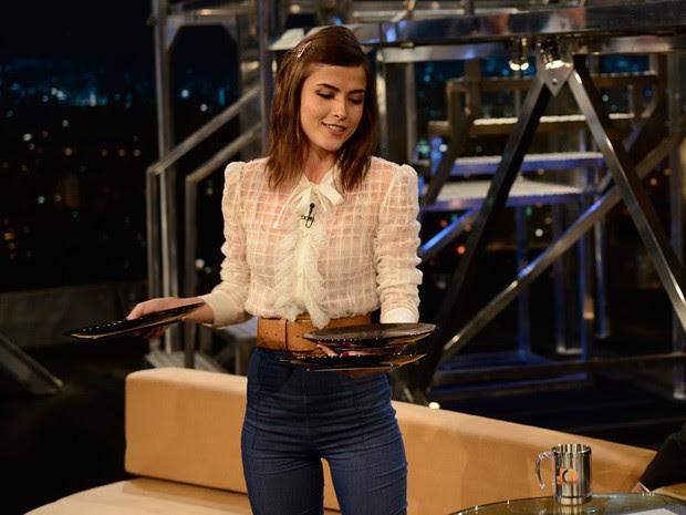 Maria Casadevall equilibra alguns pratos em seu braço (Foto: TV Globo/Programa do Jô)