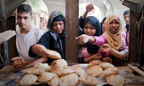 MDG : Egypt : Women buy bread from the window of a bakery in Cairo