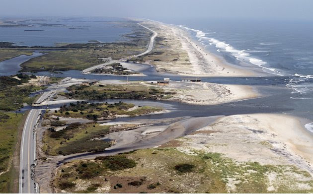 Officials survey the damage to route 12 on Hatteras Island, NC., Sunday, Aug. 28, 2011.  Hurricane Irene swept through the area Saturday cutting the roadway in five locations.  Irene caused more than