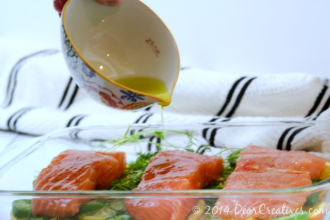 Olive oil being poured over salmon in a baking dish_DearCreatives.com