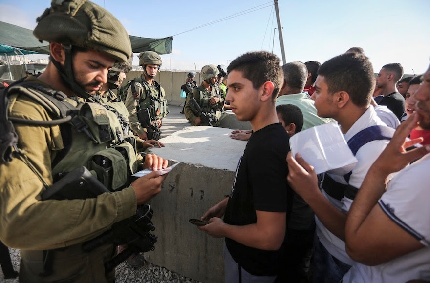 Israeli soldiers checking Palestinian ID's at the Qalandia checkpoint between the West Bank city of Ramallah and Jerusalem, July 1, 2016. (Flash90)