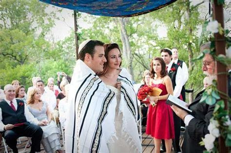 Jewish bride and groom wrapped in a prayer shawl