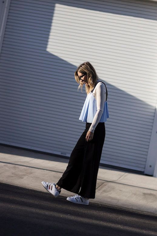 Le Fashion Blog Layering Baby Doll Tank Shirt Over White Long Sleeved T Shirt Black Wide Leg Pants White Sneakers Via The Fashion Sight