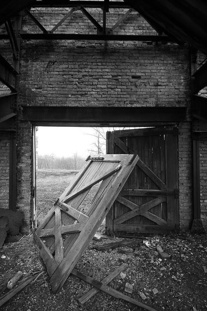 An old wooden door leaning against another door, in a brick building.
