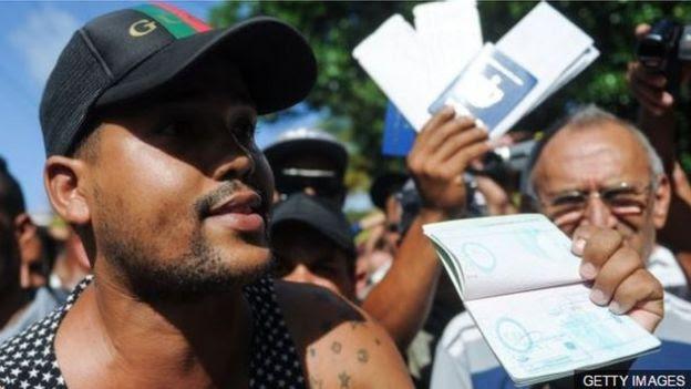 Cubanos con el pasaporte en la mano