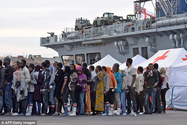 "Queue: Migrants  after disembarking from the Royal Navy ship HMS ""Bulwark"" upon their arrival in the port of Catania on the coast of Sicily"