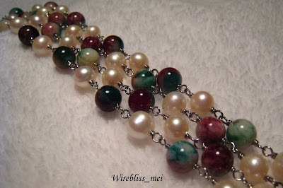 "close up wire wrap long necklace with pearl and a stone called ""Fuk Luk Sau"""